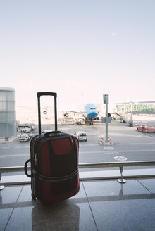 Red suitcase at airport, airplane in background - RAEF01515