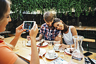 Woman taking cell phone picture of couple sitting outdoors with coffee and cake - AIF00382