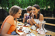 Friends with cell phone sitting outdoors having coffee and cake - AIF00385