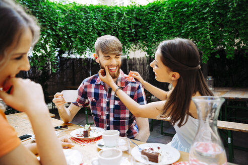 Happy young couple with friend sitting outdoors having coffee and cake - AIF00391