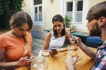 Friends using cell phones and drinking spritzer at outdoor pub - AIF00403
