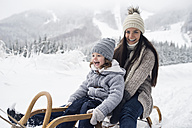 Happy mother with daughter on sledge in winter landscape - HAPF00949