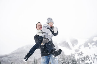 Father playing with daughter in winter landscape - HAPF00964