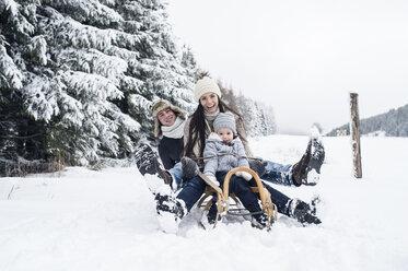 Happy family on sledge in winter landscape - HAPF00967