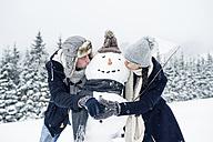 Couple kissing snowman - HAPF00976