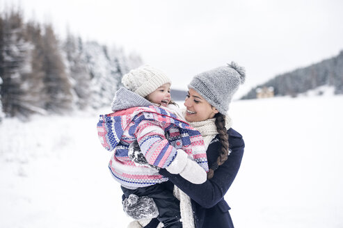 Happy mother carrying daughter in winter landscape - HAPF00988