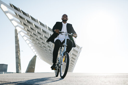 Businessman riding bicycle at solar panels - JRFF00921