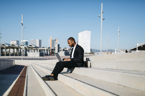 Businessman sitting on stairs with bottle of beer using laptop - JRFF00924