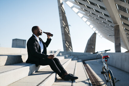 Businessman sitting on stairs drinking beer from bottle - JRFF00927