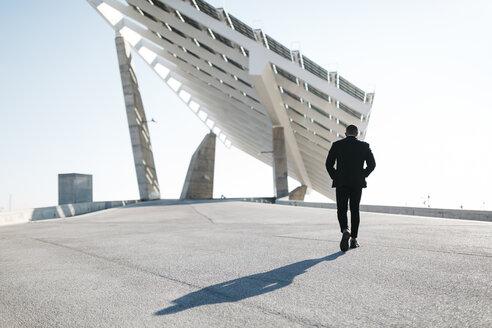 Businessman walking at solar panels - JRFF00933