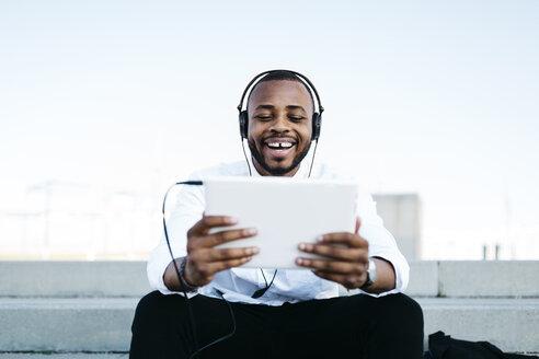 Happy man sitting on stairs wearing headphones looking at tablet - JRFF00939