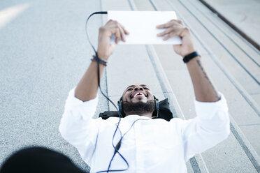 Happy man lying on the floor wearing headphones looking at tablet - JRFF00942