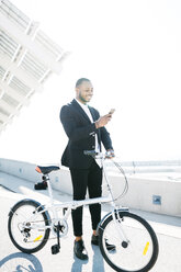 Smiling businessman with bicycle looking at cell phone - JRFF00948