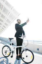 Smiling businessman with bicycle taking a selfie - JRFF00951