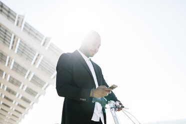 Businessman with bicycle looking at cell phone - JRFF00954