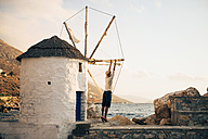 Greece, Amorgos, Aegialis, back view of man holding the blades of wind mill - GEMF01143