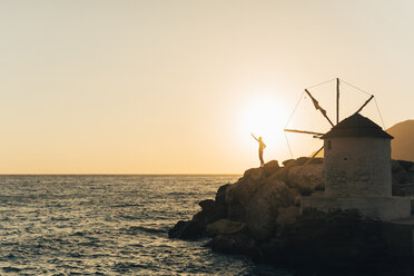 Greece, Amorgos, Aegialis, silhouette of man with raised arm near wind mill at sunset - GEMF01146