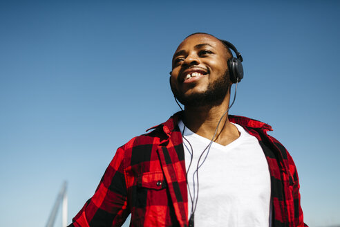 Smiling man listening to music with headphones outside - JRFF00961