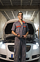 Portrait of smiling mechanic in front of car in a garage - JASF01236