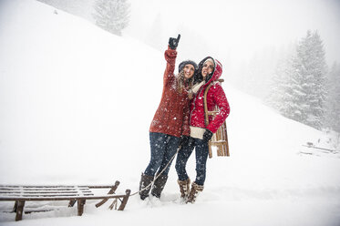 Two young women with sledges in heavy snowfall - HHF05412