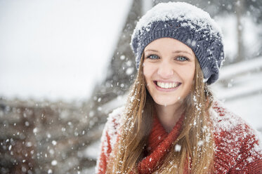 Portrait of smiling young woman in heavy snowfall - HHF05415