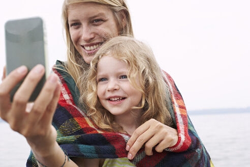 Mother with daughter wrapped in a blanket taking a selfie - FSF00585
