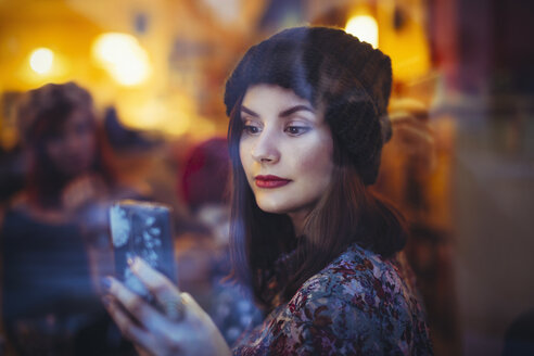Portrait of young woman with smartphone behind windowpane of a pub in the evening - LCUF00061