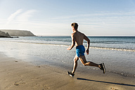 France, Crozon peninsula, young man running on the beach - UUF08627