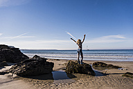 France, Crozon peninsula, teenage girl standing on rock at the beach raising her arms - UUF08642