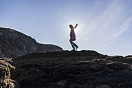France, Crozon peninsula, teenage girl walking on rock at the coast - UUF08648