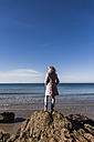 France, Crozon peninsula, teenage girl standing on rock at the beach - UUF08654