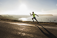 France, Crozon peninsula, young man running on coastal road - UUF08669