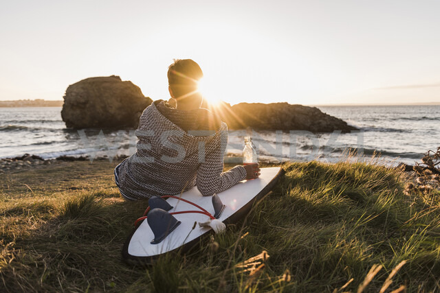 France, Bretagne, Crozon peninsula, woman sitting at the coast at sunset with surfboard - UUF08684 - Uwe Umstätter/Westend61