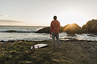 France, Bretagne, Crozon peninsula, woman standing at the coas at sunset with surfboard - UUF08687