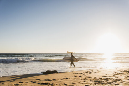 France, Bretagne, Crozon peninsula, woman in the sea at sunset with surfboard - UUF08705