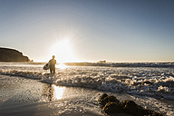 France, Bretagne, Crozon peninsula, woman in the sea at sunset with surfboard - UUF08708
