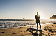 France, Bretagne, Crozon peninsula, woman standing on beach at sunset with surfboard - UUF08711