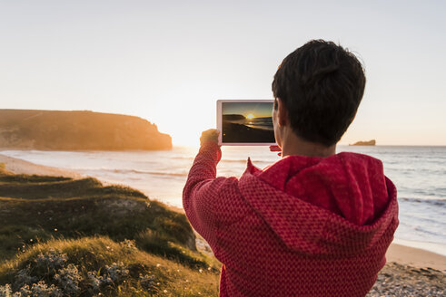 France, Bretagne, Crozon peninsula, woman at the coast at sunset taking picture with tablet - UUF08720