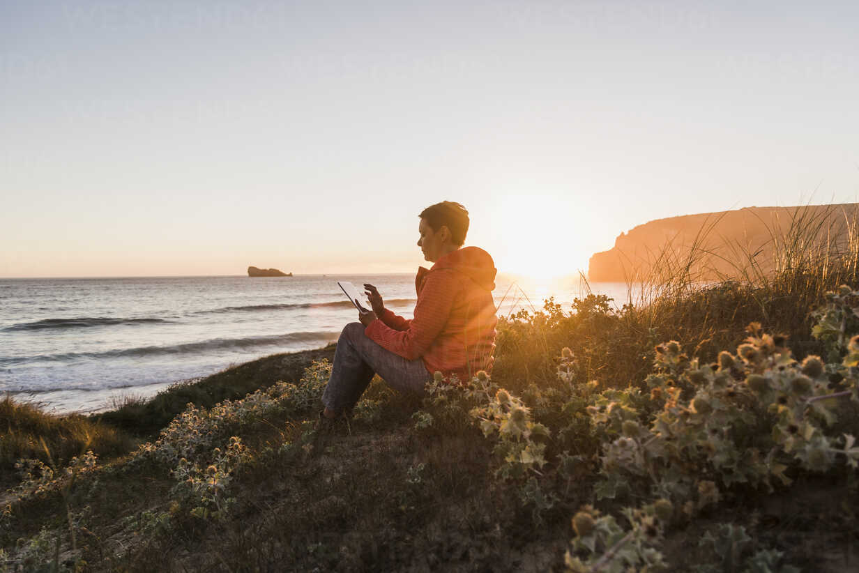 France, Bretagne, Crozon peninsula, woman sitting at the coast at sunset using tablet - UUF08723 - Uwe Umstätter/Westend61