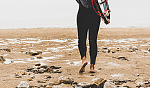 France, Bretagne, Crozon peninsula, woman walking on beach carrying surfboard - UUF08729