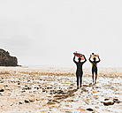 France, Bretagne, Crozon peninsula, couple walking on beach carrying surfboards - UUF08732