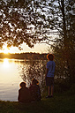 Germany, Lake Riegsee, Group of teenagers watching sunset - LBF01497