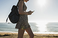 Teenage girl with backpack looking at cell phone at seaside - UUF08739