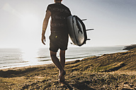 Back view of teenage boy with surfboard walking to the sea - UUF08760