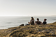 Back view of three friends relaxing at seaside - UUF08769