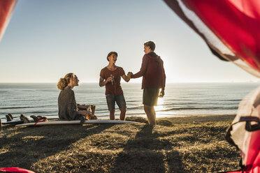 Three friends camping at seaside - UUF08790