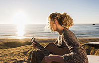 Teenage girl playing guitar at seaside in the evening twilight - UUF08793