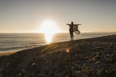 Back view of happy teenage girl with arms outstretched standing on hill at sunset looking to the sea - UUF08796