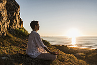 Woman meditating on cliff at sunset - UUF08802