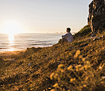 Woman sitting on cliff watching sunset - UUF08805